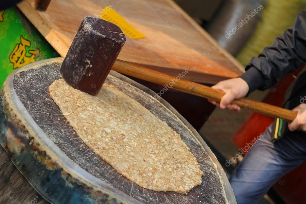 Traditional Chinese almond candy being prepared using wooden hammer on tree stump — Stock Photo #17621279