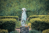 Headless statue of with a sheep in the garden — Стоковое фото