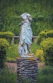 Headless statue of with a sheep in the garden — Stok fotoğraf