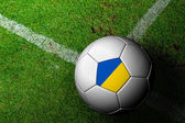 Ukraine Flag Pattern of a soccer ball in green grass — Stock Photo