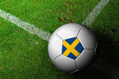 Sweden Flag Pattern of a soccer ball in green grass — Stock Photo