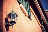 Lamp hanging on brick wall on the street — Stock Photo
