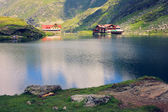 Lake and chalet at the foot of mountain — Stock Photo