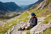 Little boy resting on mountain side — Stock Photo