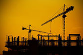 Industrial construction cranes and building silhouettes — Stock Photo