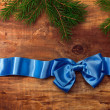 Blue satin ribbon with bow and fir branches  — Stock Photo