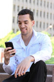 Handsome young man in white shirt chatting on mobile phone — Stock Photo