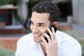 Handsome young man smiling and talking on mobile phone outdoor — Stock Photo
