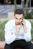 Serious young man in white shirt talking on mobile phone — Stock Photo