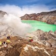 Unidentified miner harvests raw sulphur from the crater of Kawah Ijen volcano — Stock Photo