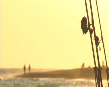 Fishing reels at sunset. Surf casting. — Stock video