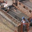 Bricklayers working in roof of house under construction. — Stock Video #13875742