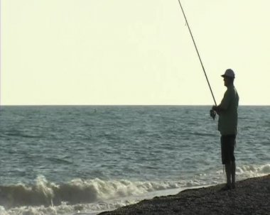 Fisherman fishing in the shore. Surf casting. — Vídeo Stock