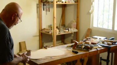 Luthier with a wood planer making a flamenco guitar — Stock Video