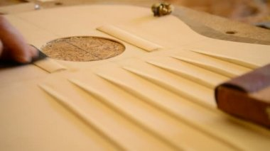 Luthier working in a guitar harmonic cover — Stock Video