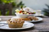 Pork pie i ogród sałatka na starym drewnianym stole w ogrodu — Zdjęcie stockowe