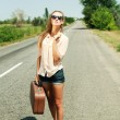 Lonely girl walking with suitcase at country road — Stock Photo