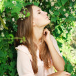 Royalty-Free Stock Photo: Young beautiful woman inhale the aroma of white flowers, in green summer garden.