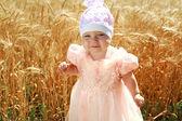 Portrait of little child girl in wheat field alone, in white hat — Stock Photo