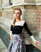 Female beauty portrait, girl in dress on the background of a brick wall old building — Stock Photo