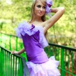 Attractive glamorous blonde girl, posing in violet dress — Stock Photo