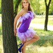 Portrait glamorous young blonde girl,flirting in violet dress, standing under the tree — Stock Photo #12364558