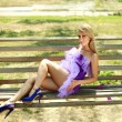 Sensual glamorous blonde girl,flirting in violet dress, siting on wooden bench — Stock Photo
