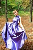 Aantrekkelijk meisje in violet lange jurk op bos — Stockfoto