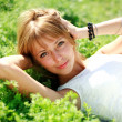 Beautiful young blonde woman on the green meadow - Stock Photo