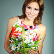 Atractive smiling brunet girl in colorful dress with flowers basket,studio shot,on gray — Stock Photo #13358864
