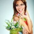 Atractive smiling brunet in colorful dress with flowers basket,studio shot,gray background — Stockfoto