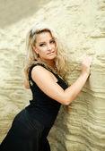 Close-up mode blond meisje in zwarte jurk poseren in zand woestijn — Stockfoto