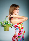 Atractive brunet girl in colorful dress with flowers basket,studio shot,gray background — Stock Photo