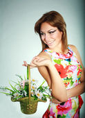 Atractive smiling brunet girl in colorful dress with flowers basket,studio shot,gray background — Stock Photo