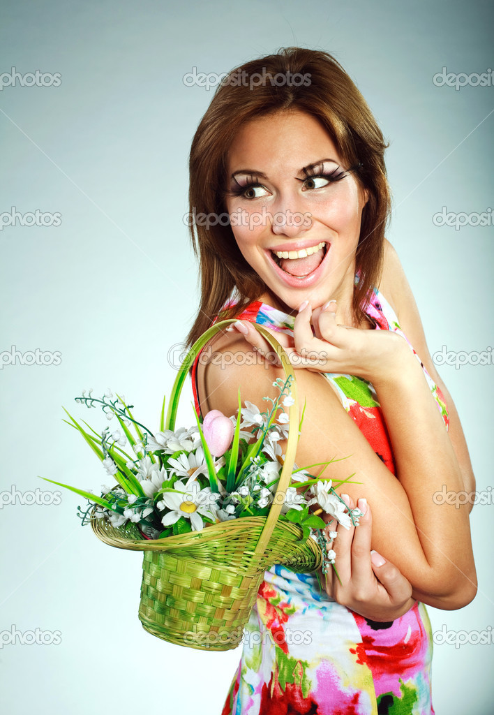 Atractive smiling brunet in colorful dress with flowers basket,studio shot,gray background — Stock Photo #13358866