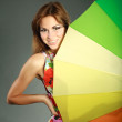 Attractive smiling brunet girl in colorful dress with rainbow umbrella ,studio shot,on gray — Stock Photo