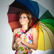 Attractive smiling brunet girl in colorful dress standing under umbrella,studio shot,on gray — Stock Photo