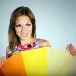 Attractive flirting brunet girl in colorful dress with rainbow umbrella ,studio shot,on gray — Stock Photo