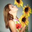 Attractive brunet girl in colorful dress, standing with sunflowers,studio shot,on gray — Stock Photo