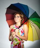 Renkli elbise daimi şemsiye, studio, gri üzerine ateş altında çekici gülümseyen brunet kız — Stok fotoğraf