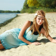Portrait of beautiful girl posing on the sand beach of river — Stock Photo