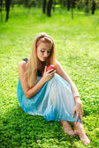 Portrait of beautiful girl in green park with red apple — Stock Photo