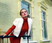 Close-up portrait stylish girl in orange pose on the background of yellow building — Stock Photo