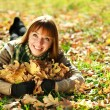 Outdoors portrait of autumn smiling girl playing with yellow leaves — Stock Photo