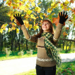 Happy girl playing with leaves outdoors in autumn park — Stock Photo