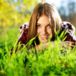 Pretty smiling young girl lying on green grass close up,in summer park. — Stock Photo #15680469