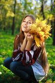 довольно смеется девушка с желтыми листьями в его руках, в зеленом парке — Стоковое фото