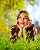 Pretty joyful young girl lying on green grass close up,in summer park. — Stock Photo