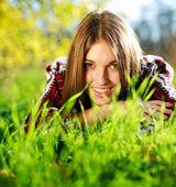 Bardzo uśmiechnięta młoda dziewczyna leżąc na zielonej trawie bliska, w lato park. — Zdjęcie stockowe