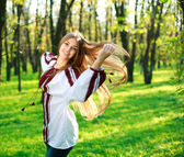 Smiling cute girl with long hair dancing in green park — Stock Photo